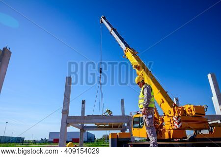 View From Behind On Construction Worker With Safety Vest And Yellow Helmet Overseeing Mobile Crane T