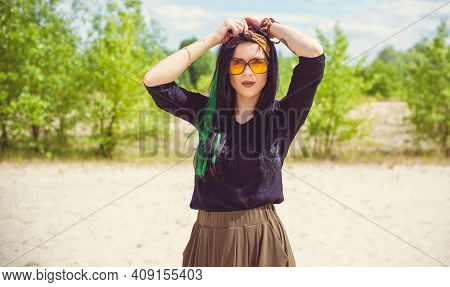 Young Hipster Woman Posing At Sand In Hippie Style And Accessory. Boho Traveler Girl In Gypsy Look.