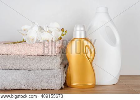 Bottles Of Detergent And Fabric Softener With Clean Towels And Orchid Flowers On Wooden Table. Conta