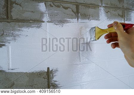 A Construction Worker Applies Paint To A Brick Wall.the Painter Paints Primers The Walls With A Brus