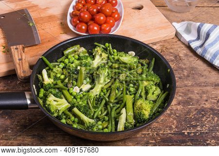 Cooking Green Vegetables For Pasta In A Frying Pan - Beans, Broccoli, Asparagus, Peas And Spinach In