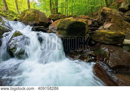 Small Waterfall In The Forest. Clean Water Of A Mountain River Flows Among Rock. Spring Nature Backg