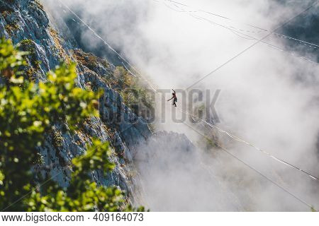 A Man Walks Along A Stretched Sling High Above The Clouds. Highliner Catches The Balance On A Long A