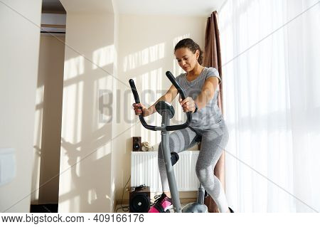 Beautiful Sportswoman Cycling A Bike At Home. Cardio Training, Exercising Legs, Cardio Workout At Ho