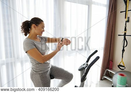 Happy Woman Checking Her Fitness Tracker And Heart Rate While Standing On A Spin Bike After Cardio W