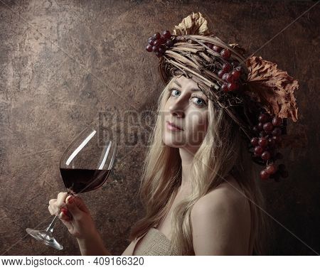 Portrait Of Beautiful Blonde With Glass Of Red Wine. Shy Image Of A  Blonde Nymph In A Wreath Of Vin