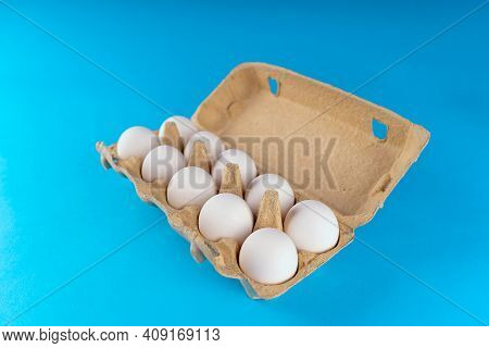 Farm Raw, Fresh White Chicken Egg In An Egg Box On A Blue Background. Eggs In Carton. Eggs In The Ba