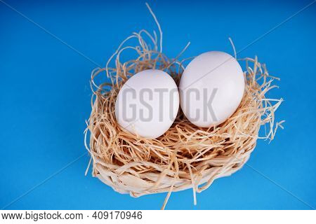 Farm Raw, Fresh White Chicken Egg In A Basket On A Blue Background. Concept: A Fresh Egg For The Mor