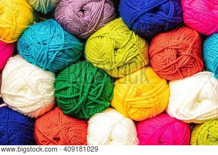 Balls of colourful crochet yarn and knitting wool stacked high for a new lock-down hobby