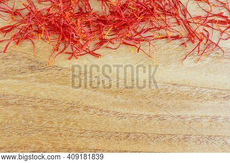 Dry Saffron Stigmas On A Wooden Surface. Place For Your Text. Saffron .