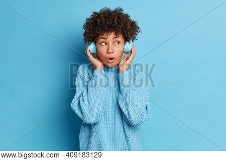 Horizontal Shot Of Surprised Young African American Woman Keeps Hands On Stereo Headphones Listens F