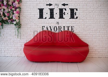 Red Sofa Lips Shape On White Brick Wall Background. Minimalism Concept. Sofa Lips In White Room And