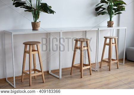 Simple Sitting Area With Table, High Chairs And Plant In Pots. Minimalist Design With Of Table And H
