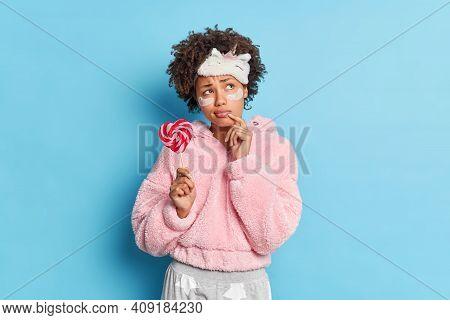 Sad Displeased Dark Skinned Woman Looks Pensively Aside Holds Delicious Lollipop Going To Sleep Appl