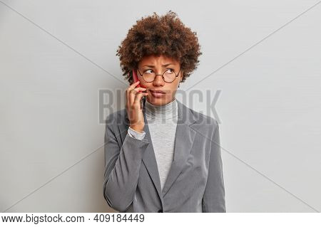 Corporate Communication Concept. Serious Displeased African American Woman Talks Via Modern Mobile P