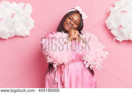 Photo Of Pleased Overweight Dark Skinned Brunette Woman Tilts Head Feels Satisfied Wears Headband An