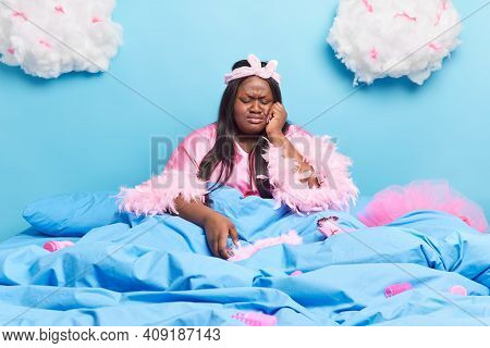 Frustrated Lonely Dark Skinned Obese Woman Wears Pink Dressing Gown Has Dejected Face Expression Pos