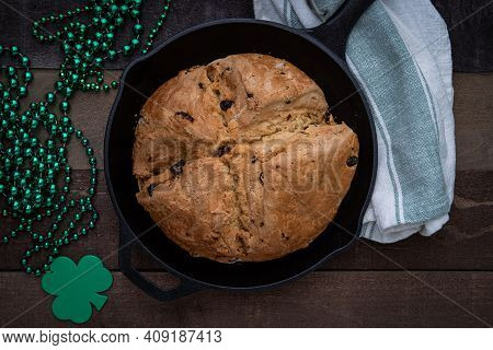Photograph Of Irish Soda Bread Baked In A Cast Iron Skillet With Shamrock Beads For Saint Patrick's