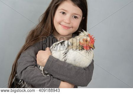 Little Girl Holdinig White Cockerel With Black Feathers