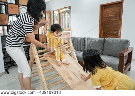 A Woman Patiently Holding A Baby While Standing Sliding On A Pikler Triangle Toy