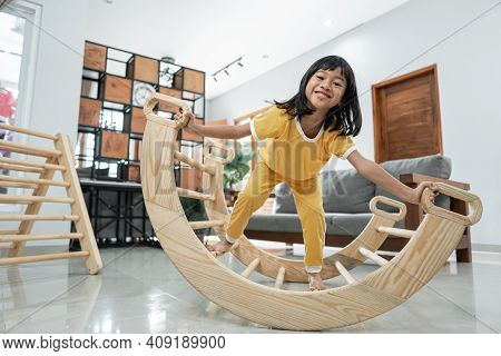Little Girl Smile While Playing Balance In Pikler Triangle Toy