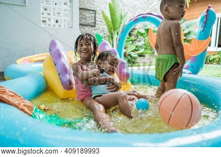 Big Sister Smiles Hugging Younger Sister While Playing Together In Rubber Pool Portable
