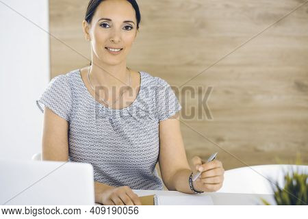 Cheerful Smiling Businesswoman Working With Laptop Computer While Sitting At The Desk In Modern Offi