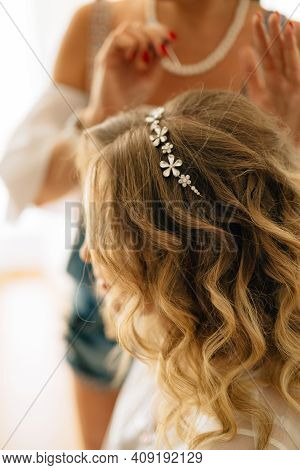 Stylist Puts On A Hairpin In The Brides Hairstyle During Wedding Preparations