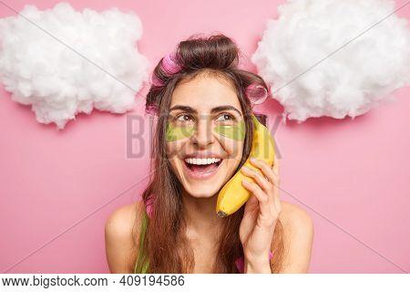 Headshot Of Positive Brunette European Woman Applies Hair Rollers Makes Hairstyle Wears Hydrogel Pat