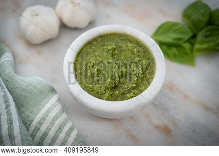 Photograph Of Fresh Basil Pesto, On The Counter In A Stoneware Bowl, With Garlic And Basil Leaves In