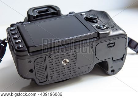 Photo Camera On White Background, Bottom View Of Professional Dslr Camera Body. Black Digital Camera