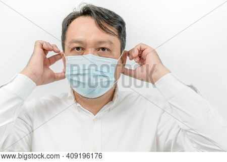 Portrait Of Asian Man In White Shirt Wearing Face Medical Mask For Protection From Virus Disease Iso