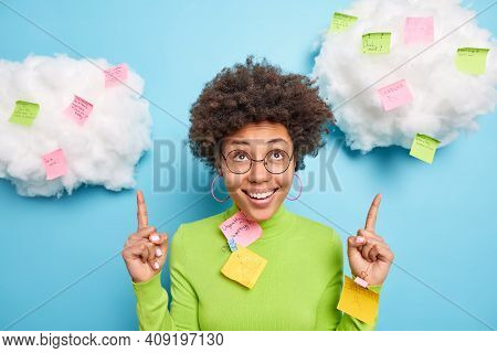 Positive African American Woman Smiles Toothily And Points Above Being In Good Mood Surrounded With