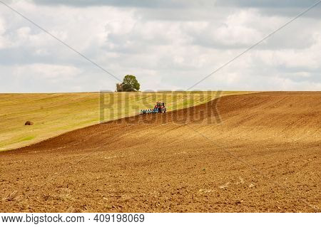 A Tractor With A Large Plow Plows A Hilly Field. Tractor With Agricultural Equipment.