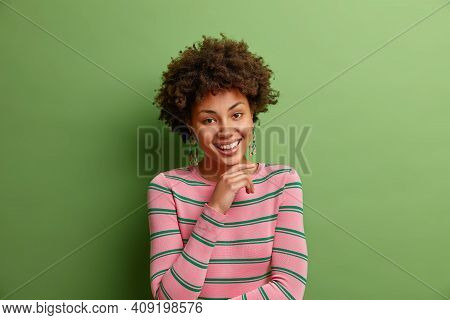 Portrait Of Good Looking Curly Haired Woman Keeps Hand Under Chin Smiles Broadly Has Pleased Face Ex