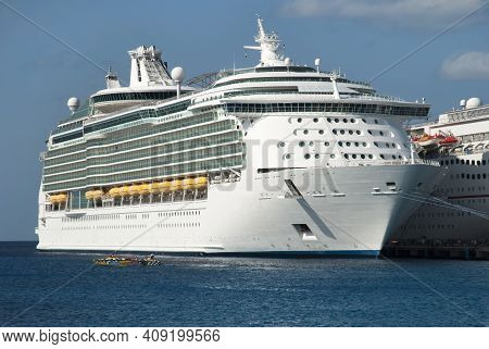 The Racing Motorboat Passing By Large Cruise Ship Moored In San Miguel On Cozumel Island (mexico).