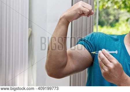 Close Up Of A Man Injecting Steroid Into The Biceps.
