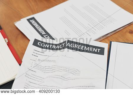 The Torn Contract Paper Placed On The Table After Negotiation Fails. The Concept Of Contract Termina