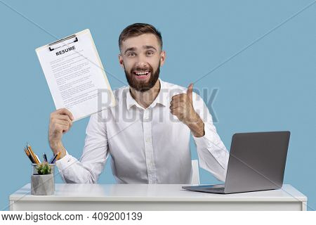 Happy Caucasian Guy Holding Resume And Showing Thumb Up Gesture At His Desk, Blue Studio Background.