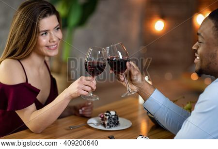 Happy Interracial Couple With Glasses Of Red Wine Having Date In Restaurant, Making Toast For Love.
