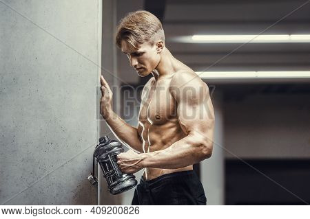 Fitness Man In Gym Drinking Water After Workout Looking At Cell Phone. Fitness And Bodybuilding Heal
