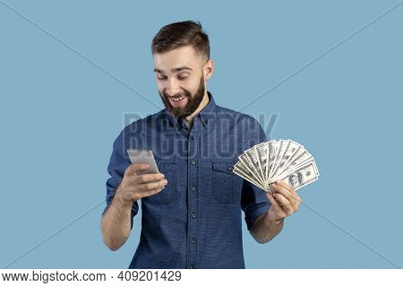 Cheerful Young Man With Money And Cellphone Winning Lottery Or Casino Bet On Blue Studio Background.