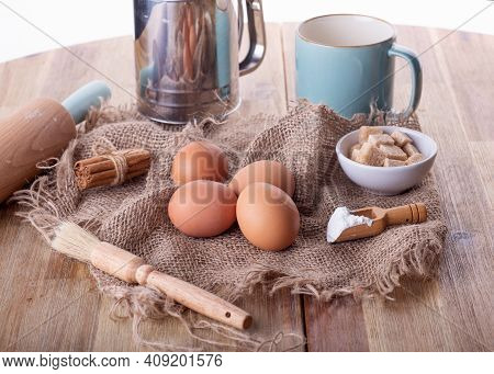 Baking Ingredients Eggs, Sugar, Baking Powder,  Cinnamon For Baking On A Wooden Table