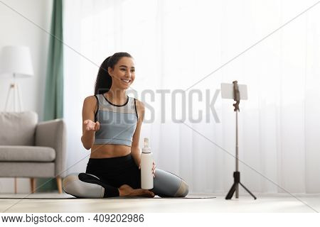 Cheerful Young Woman In Sportswear Fitness Trainer Sitting On Yoga Mat, Holding Bottle Of Water, Bro
