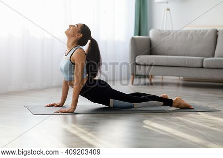 Flexible Young Woman In Sportswear Practicing Yoga At Home, Laying On Yoga Mat In Living Room And St