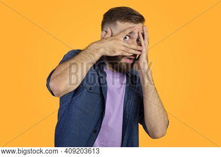 Scared Caucasian Guy Hiding Behind His Hands, Peeping Between Fingers On Orange Studio Background. H