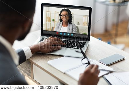 Business Video Call. Black Male Entrepreneur Having Online Meeting With Female Colleague Through Tel
