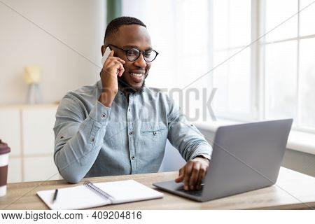 Happy Black Businessman Talking On Cellphone Having Phone Conversation Sitting At Workplace Working