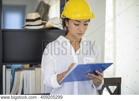 Asian Women Engineering Inspecting And Working And Holding Blueprints At Home Office