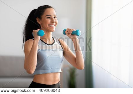 Closeup Of Cheerful Young Woman Doing Dumbbell Workout At Home, Working On Arms Strength, Looking At
